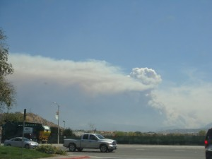 Wildfire smoke battles fluffy cloud.