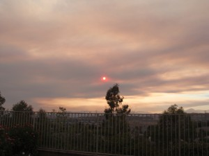 sun obscured by smoke clouds from wildfires appears to be glowing red