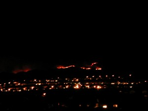 wildfires at night seen beyond lights of the city in the faraway hills