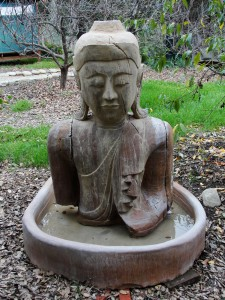 buddha statue sitting outside yoga studio