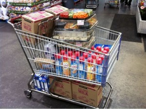 shopping cart filled with cases of milk, creamer, sugar, sandwiches, and veggies