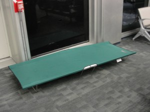 cot sits on ground in jfk for travelers who need a place to sleep