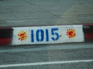 bright sun design painted on curb next to street number