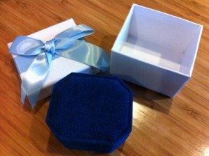 white outer box with ribbon and fuzzy blue inner box