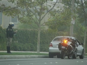 motorcycle cop pulls over a car