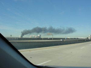 dark smoke stack emerging from flame in the distance, from a plant burning things