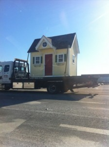 very small house on flatbed tow truck
