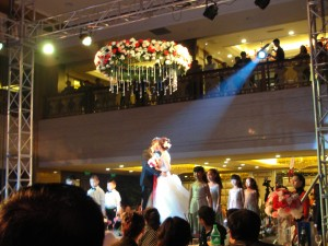 the bride and groom share a kiss as they are elevated by a platform