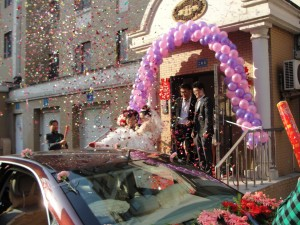 groom carries bride out of her house into waiting car as confetti rains down