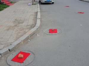 red paper held down by red bricks cover sewage caps