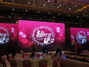 huge screen in ballroom of hotel with custom wedding theme logo displayed