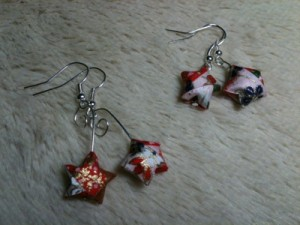 two pairs of star-shaped origami earrings made with red, white, cream, blue, green, brown, and gold japanese design