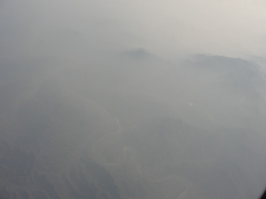 hazy view of ground below from airplane