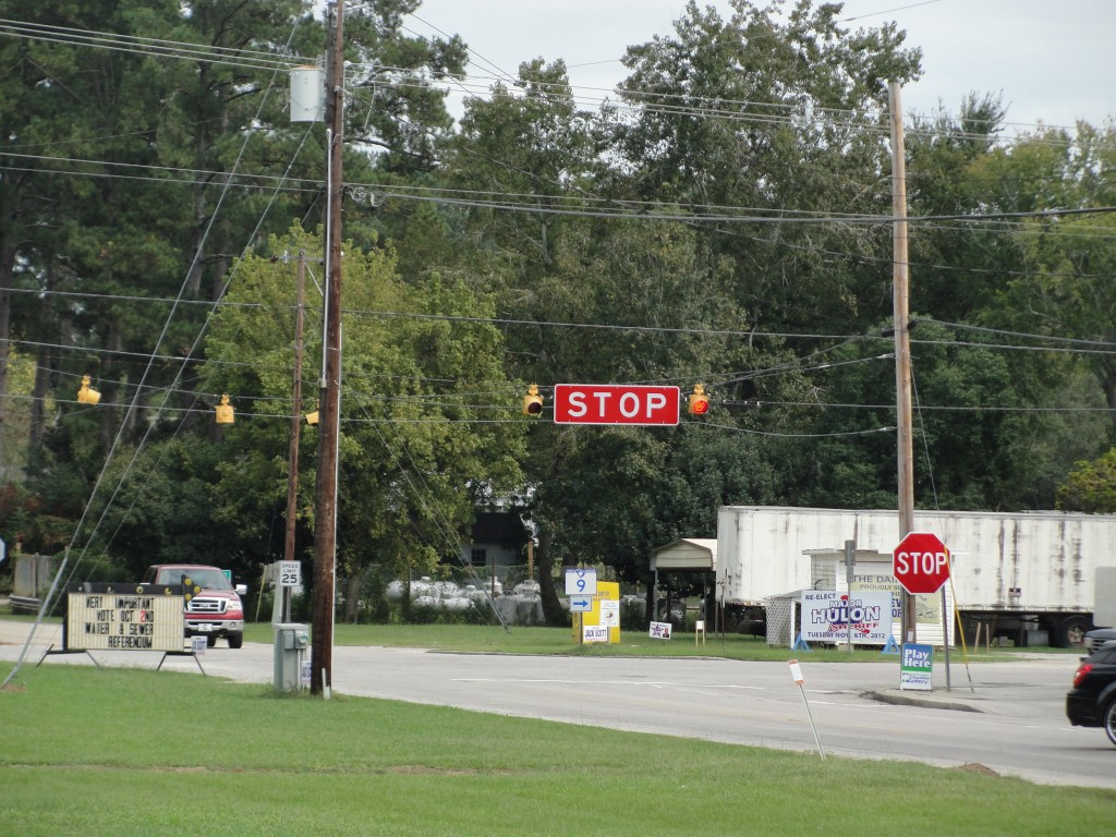 huge stop sign hanging like street sign over intersection