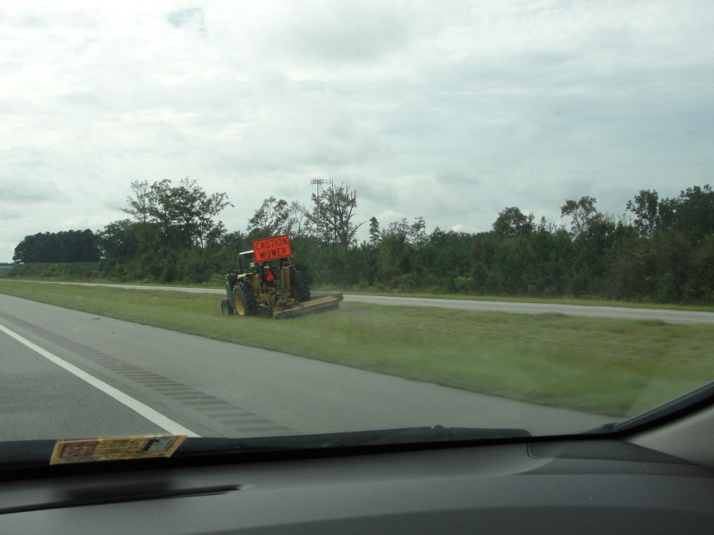 lawn mower vehicle driving along side of freeway mowing grass