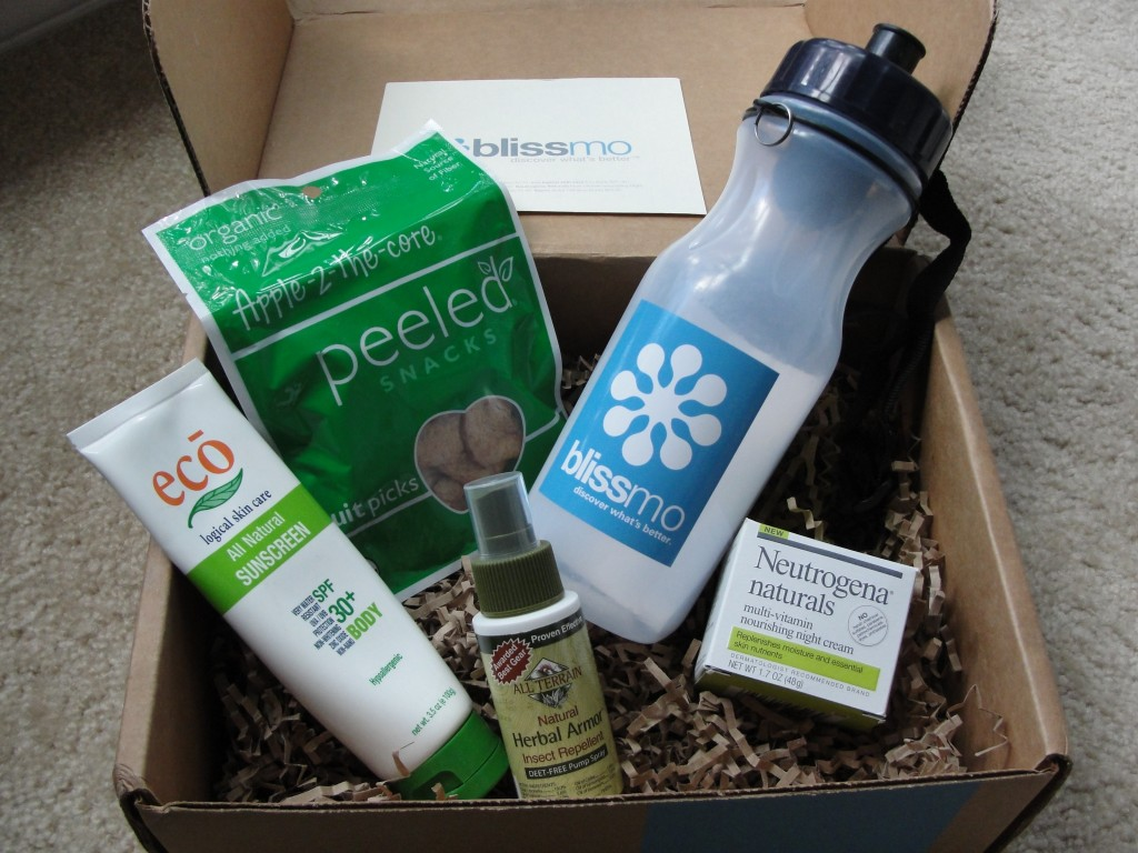 contents of blissmobox anniversary edition including eco logical sunscreen, peeled snacks apple-2-the-core, bates water filtration bottle with blissmo logo, all terrain insect repellent, and neutrogena naturals night cream