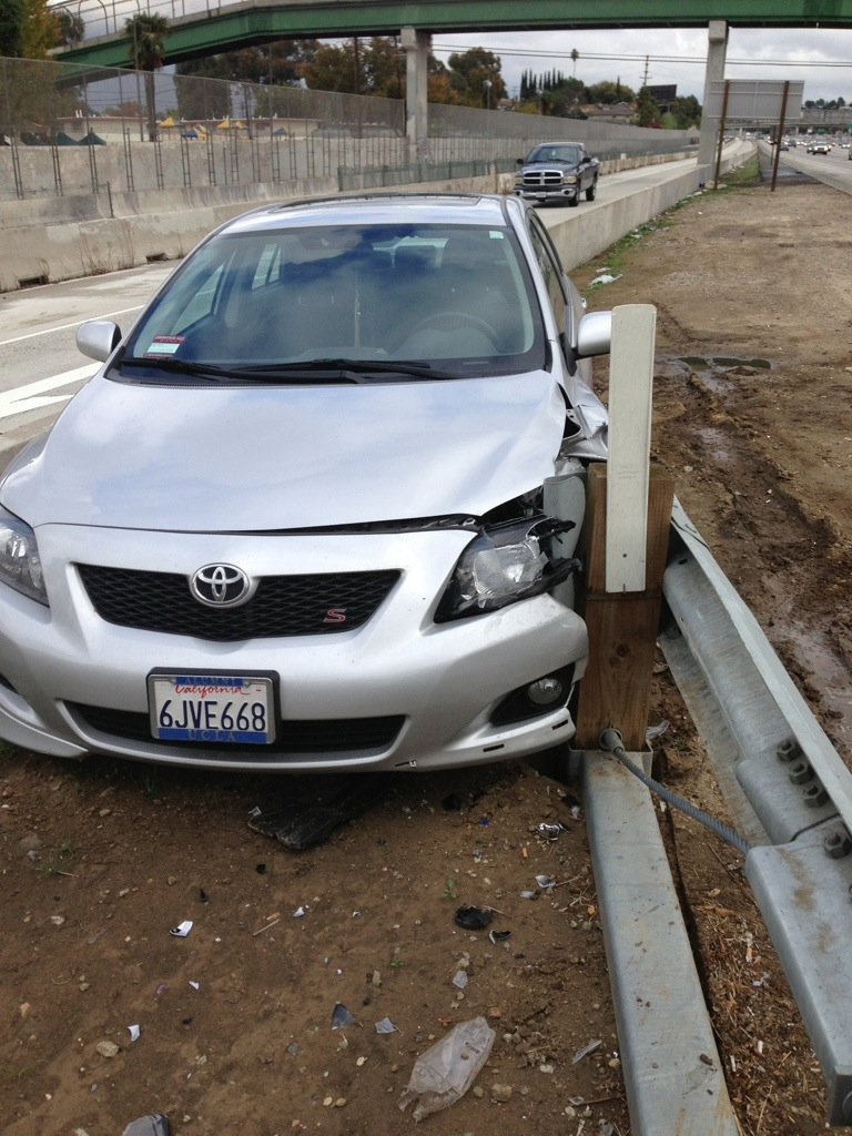 front left of car smashed into guardrail at side of highway