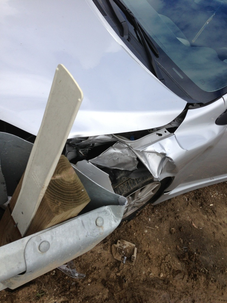 front left car wheel and bumper smashed into guardrail