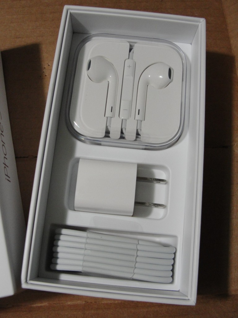 inside of iphone 5 box with accessories showing: earpods, charging cable, and charging plug