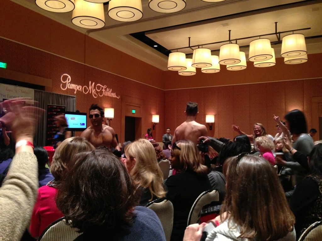 expert corner stage at pamper me fabulous with shirtless guys giving out hats