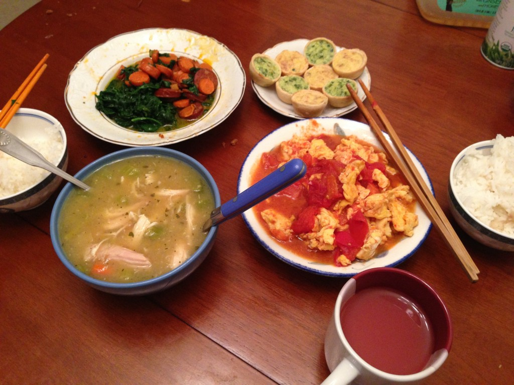 meal consisting of chicken noodle soup, sausage with carrot & spinach, mini quiches, tomatoes & eggs, rice