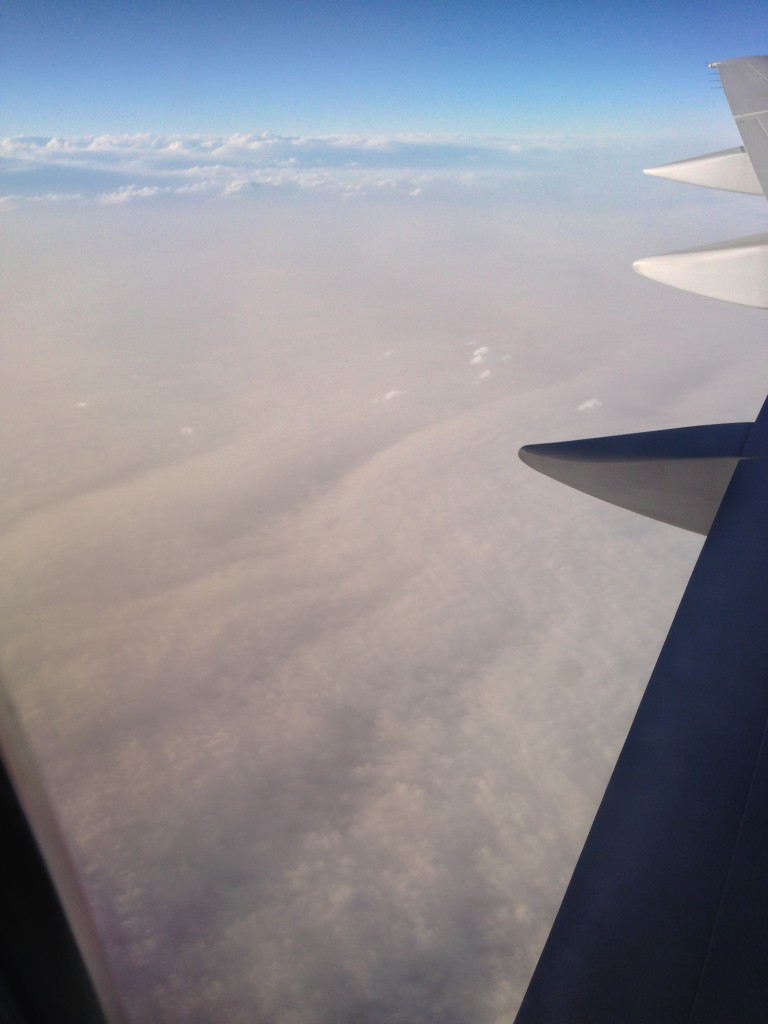 view from plane of sky covered in dust-like clouds