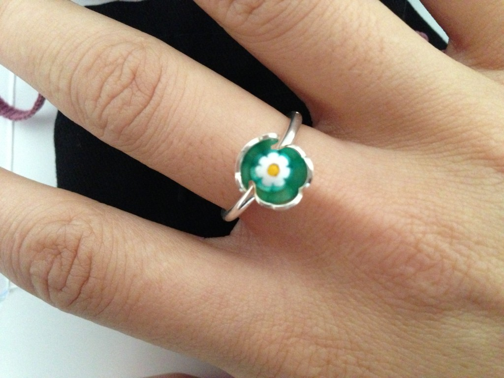 wearing tous bear green & white flower ring on finger
