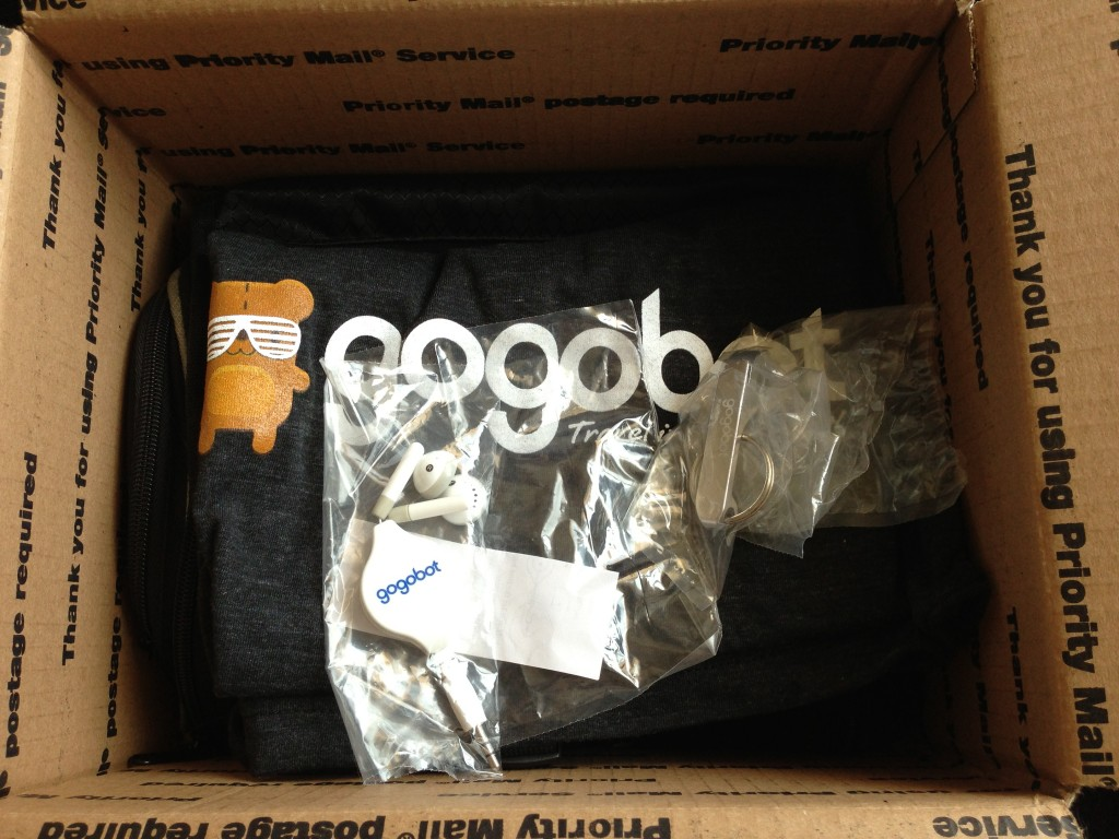 gogobot box of swag with (headphones, bottle opener keychain, t-shirt, and fancy toiletry bag