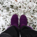 purple winter shoes against light layer of snow on grass