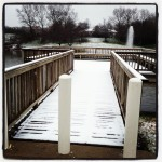 wooden plank walkway over pond covered in layer of snow