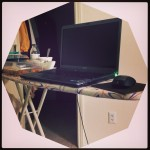 laptop sitting on ironing board used as desk
