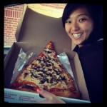 girl smiling with giant slice of jumbo pizza cheese with mushrooms