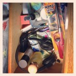 drawer filled with various skincare and home items including utility lighter and headphones