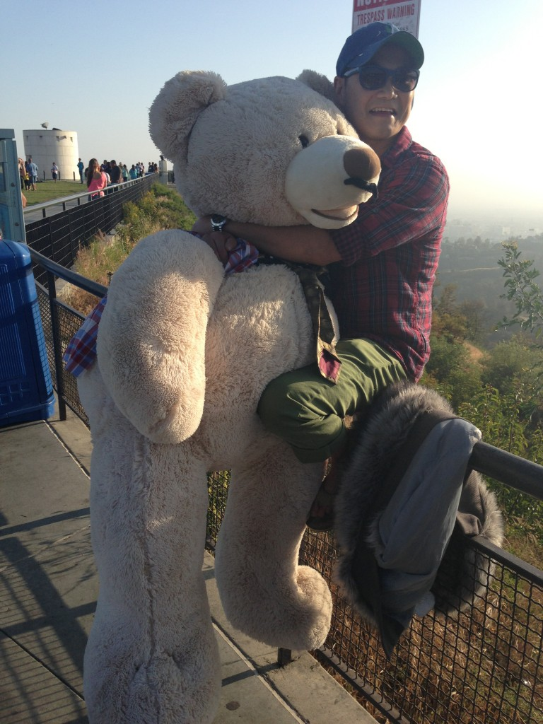 guy hugging giant teddy bear at griffith observatory while sitting on fence