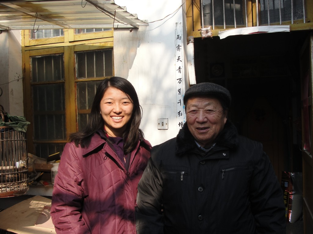 chinese granddaughter and grandfather standing outside doorway in winter