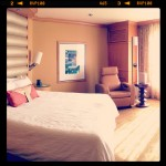 sunlight shining into nice hotel room with king bed and leather furnishings
