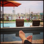 lounging by pool overlooking harbor with feet in shot