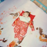 chinese baby laying on bed wrapped in red flower swaddling clothes with red pillow and red dot on forehead