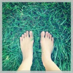 bare feet standing on lawn of green grass