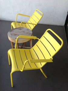 two yellow porch chairs and a wooden table on porch of room at hotel maya