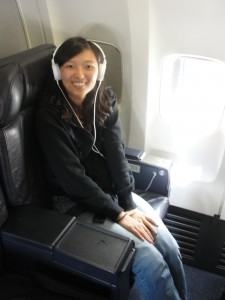 sitting in first class seat of plane with headphones on
