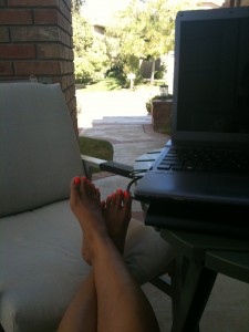 sitting on front porch with legs extended working on laptop