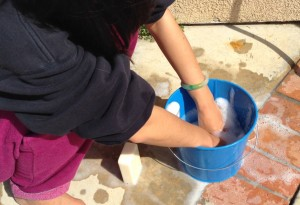 cleaning with hands in blue metal bucket/pail filled with soapy water