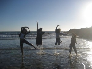 four people jumping on beach spelling out rlcc