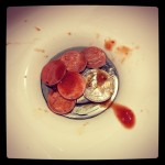 pile of coins in sink with hot sauce on top