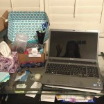 desk covered with laptop, boxes, and other items