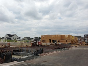 the three stages of the villas being built: foundation poured, frame up, and exterior completed