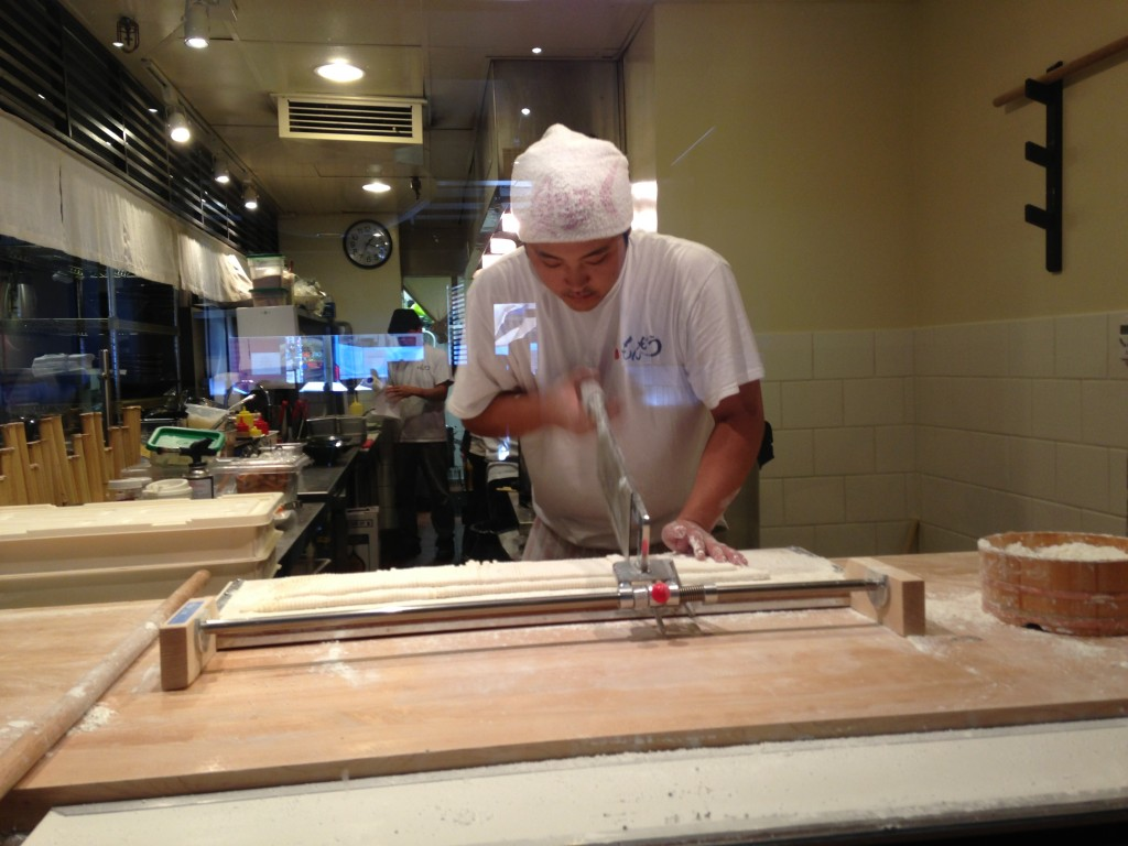 chef at japanese restaurant chopping line of udon noodles