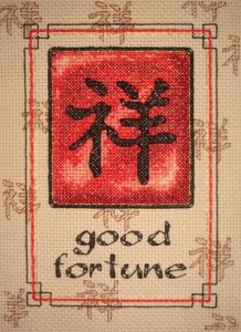 red, black, brown, and gold cross stitch pattern with chinese character and good fortune message