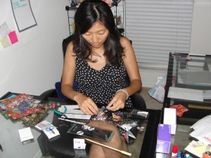 sitting at desk working on making origami jewelry
